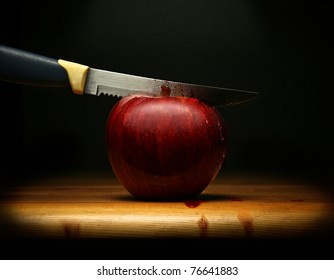 A knife cutting a red apple and blood flowing, on dark background.