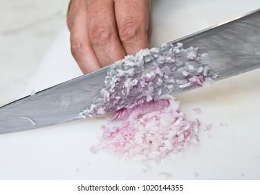 A knife dicing fresh organic Shallots, on a white cutting board.