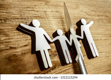 knife divides the whole family. divorce idea. wooden figure. wood background.