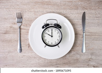 knife and fork with alarm clock on white plate on tablecloth background. Intermittent fasting, Ketogenic dieting, weight loss, meal plan and healthy food concept