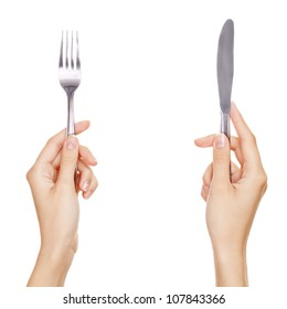 A knife and fork being held by womans hands. Isolated on white.