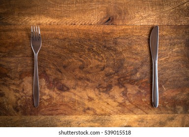 Knife and fork with missing plate on wooden table, top view