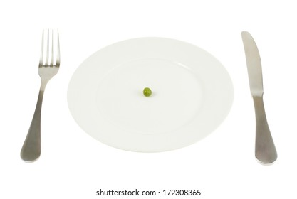 Knife and fork next to a plate with a single green pea isolated over white background