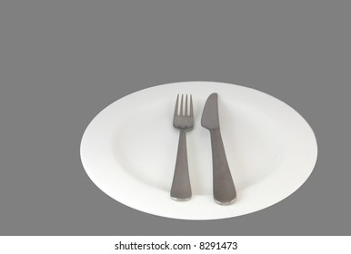 Knife and fork on a plate isolated against a grey background