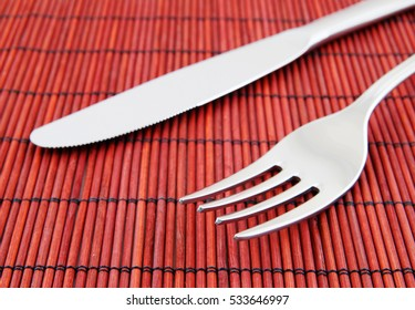 Knife and fork on red bamboo mat.