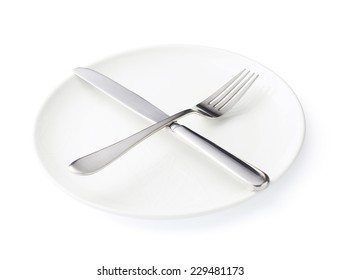 Knife and fork over the empty white ceramic plate isolated over the white background