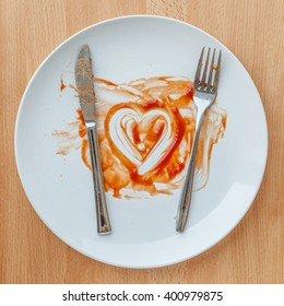 Knife and fork over in finish plate and heart shape ketchup, concept of tasty.