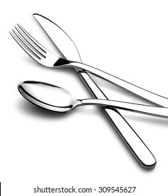 knife fork and spoon in crossed position on white background