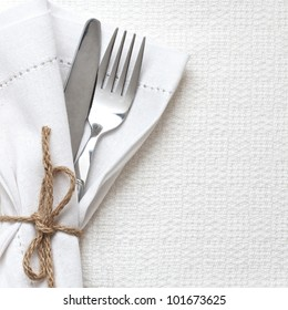 Knife and fork with white linen tied up with string