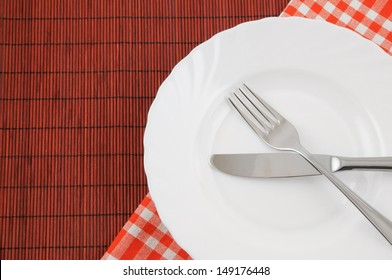 Knife and fork in white plate on red bamboo background with tablecloth