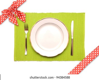 The knife, fork and white plate on a green napkin with dotted red satin gift bow and ribbon on a white background