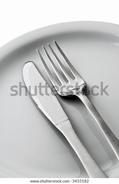 knife, fork and a white plate on white
