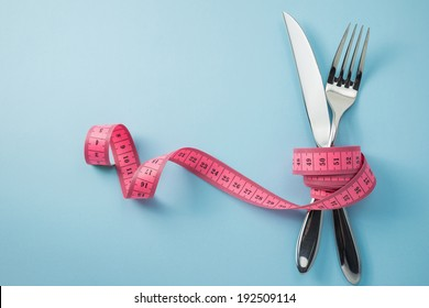 Knife and fork wrapped in tape measure on blue background