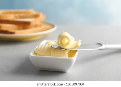 Knife and gravy boat with butter curls on table