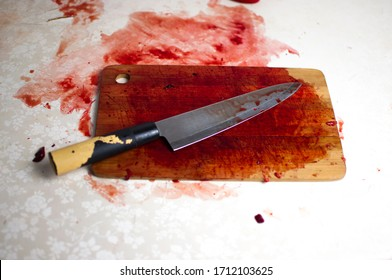 knife with grunge of blood on wood cutting board