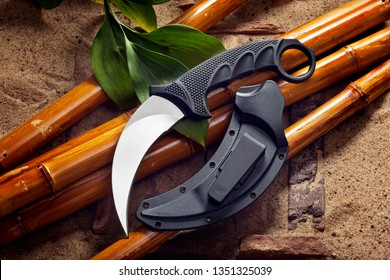 Knife karambit with scabbard lies on bamboo trunks.