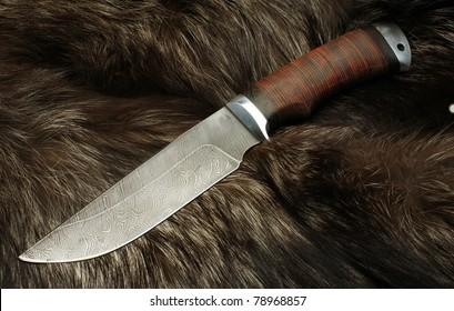 Knife on fur of a black fox