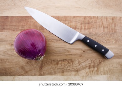 Knife, Red Onion and a Cutting Board