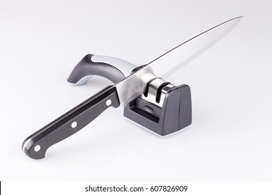 Knife and knife sharpener on a white surface. Kitchen tools isolated on white background.