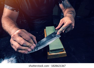 Knife sharpening. Close up of hand sharpening the chef knife