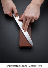 Knife sharpening. Close - up of heand are sharpening the chef khife. Dark background.
