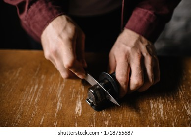 Knife sharpening process. A man holds a knife in his hands. Close-up view. Wooden background.