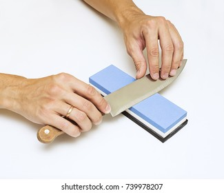 Knife sharpening with whetstone sharpener or grindstone, The abrasive which sharpen the knife blade, man using a knife grinder, man hand sharpenes knife on white background