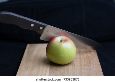 a knife sliceing a honeycrisp apple on cutting board.