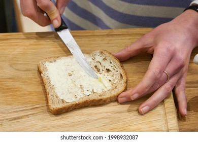 Knife spreading butter on toast bread in womens hands in the morning breakfast. Coffee and dessert concept. High quality photo