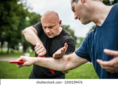 Knife vs knife fight. Kapap instructor demonstrates martial arts self defense fighting and disarming technique. Weapon retention and disarm training