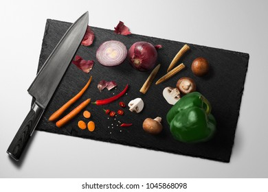 Knife,paprika,onion,carrot on cutting board.