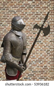 Knight in armor in front of a castle's wall