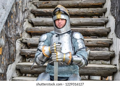 Knight in the armor on the wooden steps. Knightly armor and weapon. Semi - antique photo.