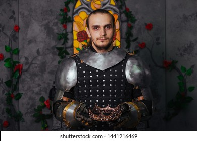 Knight in the castle with a crown in his hands. Coronation. A man in armor holds a crown.