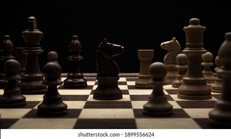 Knight in a chess duel on the chessboard. Low-key concept picture of chess pieces taken in studio and concerning decision making and strategy.