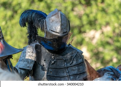 Knight in full plate armor with a blue feather on his helmet and holding a joust