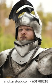 Knight in helmet and armour before battle on forest background