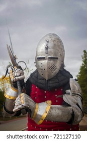 Knight in helmet and red brigantine against the background of thunderclouds. With a two-handed sword in his hands. Attacks