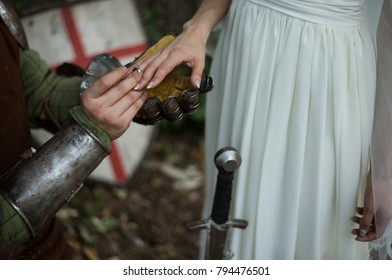 The knight makes an offer to the bride. The ring on bride's finger