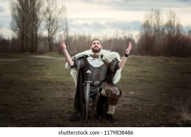 Knight raised his hands to the sky in pleading, wearing a chain mail.