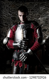 Knight Standing With Head Bowed in Prayer And Metal Sword, Stone  Wall Background