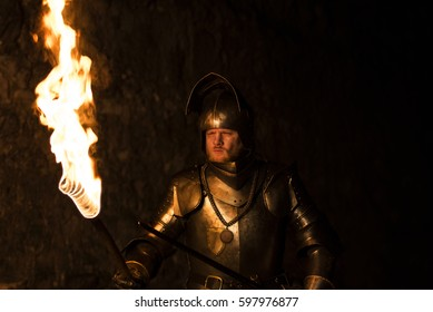 Knight with a torch and sword at night on a wall background.Adventure