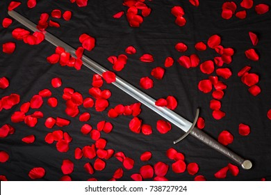 knightly sword and red rose petals on a black cloth