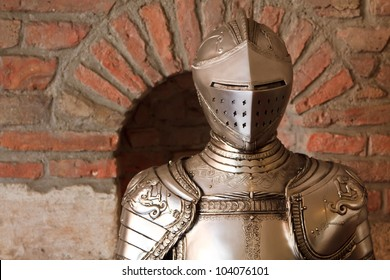 A knight's armour with shining metal and ornate shield and sword