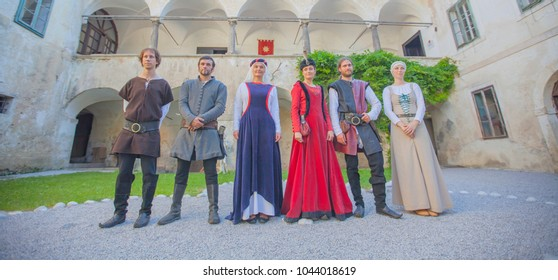 Knights and princesses are standing together in line on a courtyard.