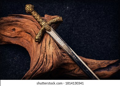 Knight's sword on the background of an old textured wooden driftwood of brown color