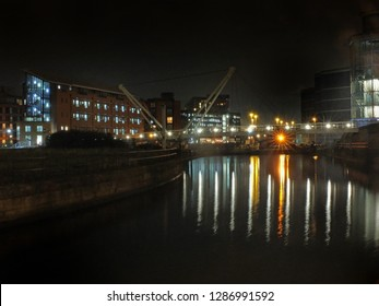Knights Way Footbridge crossing the river aire at the lock entrance to clarence dock in leeds at night with buildings and lights reflected in the water