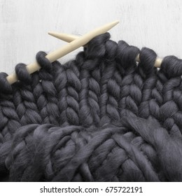Knit of black super chunky woolen yarn with wood needles on rustic white wooden background.