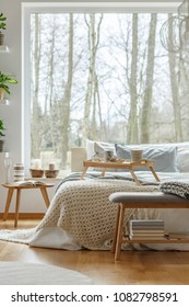 Knit blanket on bed next to wooden table against the window in natural bedroom interior of a house