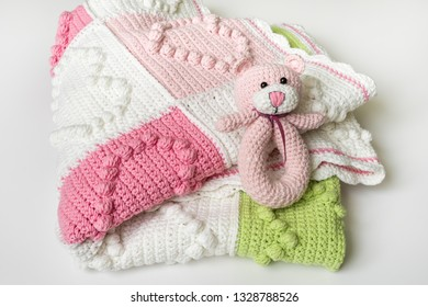 Knitted baby blanket with decorations in heart shape and small pink teddy bear toy